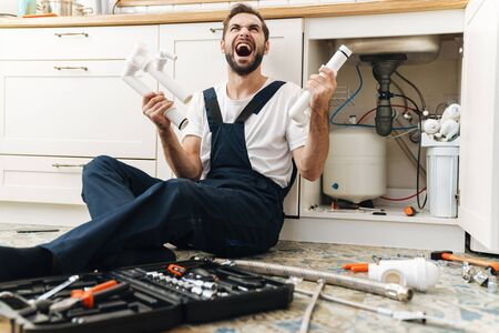 Photo of young screaming displeased emotional man plumber work in uniform indoors holding pipe.