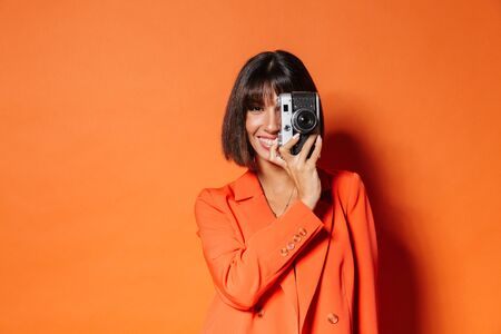 Beautiful smiling young woman wearing jacket standing isolated over orange background, taking picture with photo camera Reklamní fotografie