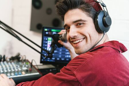 Image of young happy caucasian dj man wearing headphones working at radio station while making podcast recording for online show