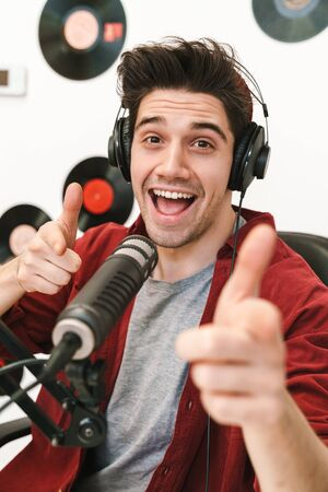 Image of young happy caucasian man performing at radio program while making podcast recording for online show
