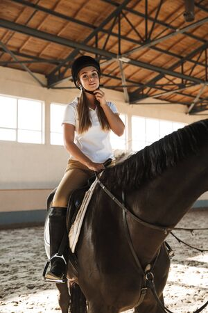 Picture of smiling pleased young blonde beautiful woman wearing hat with horse in countryside in corral on training area. Standard-Bild