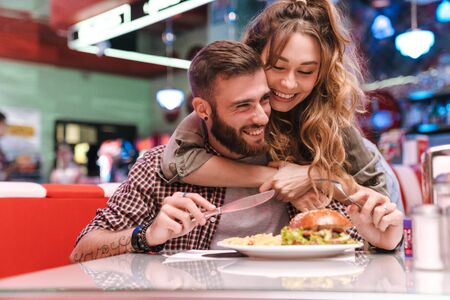 Photo of a cute happy positive young loving couple in retro bright street food cafe hugging.