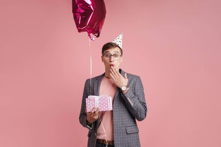 Image of a shocked young boy in glasses in birthday cap isolated over pink wall background holding present gift and star balloon.