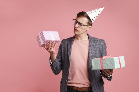 Image of a young thinking serious guy in glasses holding birthday present gift boxes isolated over pink wall background. Imagens