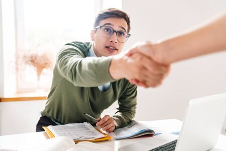 Photo of a young guy indoor in office wearing eyeglasses shaking hand of his colleague.