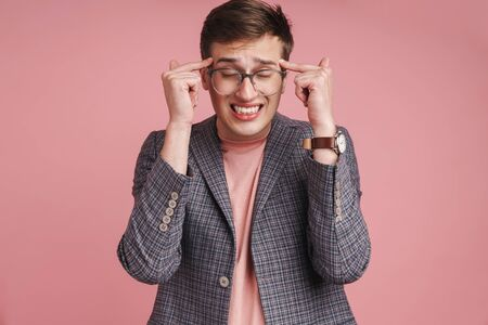 Photo of a young stressed displeased boy with headache in glasses isolated over pink wall background.