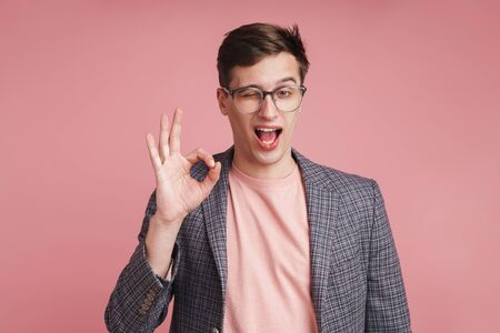 Image of a young boy in glasses isolated over pink wall background showing okay gesture.