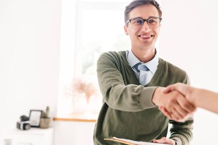 Image of a happy young guy indoor in office wearing eyeglasses shaking hand of his colleague.