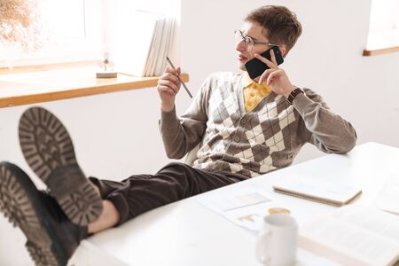 Image of a confused young guy student sit at the table indoors talking by mobile phone studying.