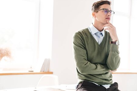 Image of a thinking thoughtful young guy student sit on table indoor in eyeglasses.