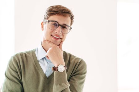 Image of a cheerful smiling young guy student posing indoor in eyeglasses.