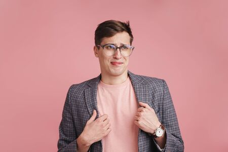 Photo of a young confused boy in glasses isolated over pink wall background.