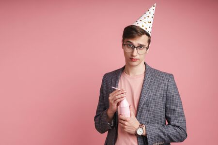 Portrait of an upset young man wearing birthday hat celebrating isolated over pink background, holding a drink