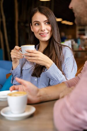 Close up of an attractive young couple in love having lunch at the cafe indoors, drinking coffee