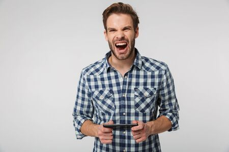 Portrait of excited young man wearing plaid shirt screaming and playing video game on cellphone isolated over white background