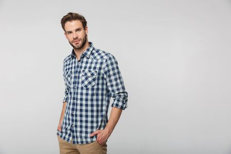 Portrait of unshaven young man wearing plaid shirt posing on camera with hands in pockets isolated over white background