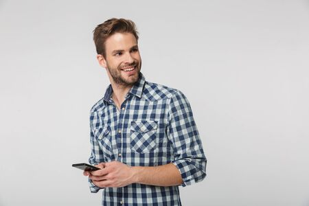 Portrait of happy young man wearing plaid shirt smiling and using cellphone isolated over white background