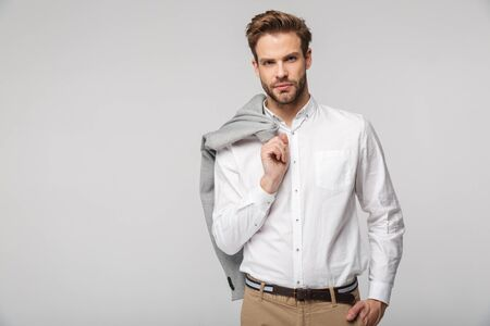 Portrait of confident young man wearing shirt posing on camera with jacket isolated over white background