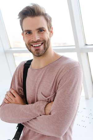 Image of young bearded man with bag smiling while standing over bright window indoors