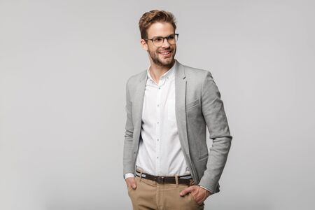 Portrait of happy young businessman in eyeglasses posing at camera and smiling isolated over white background