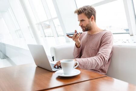 Image of young bearded man using smartphone and laptop while sitting on sofa by window in cafe indoors