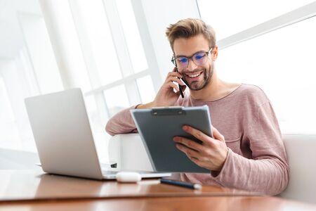 Image of young bearded man talking on cellphone and holding clipboard while working in cafe indoors