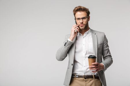 Portrait of serious handsome man in eyeglasses talking on cellphone and holding paper cup isolated over white background