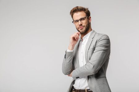 Portrait of caucasian young man in eyeglasses posing at camera and looking aside isolated over white background