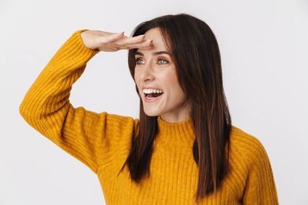 Image of excited brunette adult woman wearing sweater looking aside with hand at her forehead isolated over white background