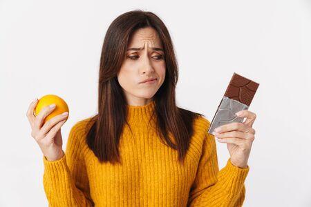 Image of doubtful brunette adult woman hesitating while holding orange and chocolate bar isolated over white background