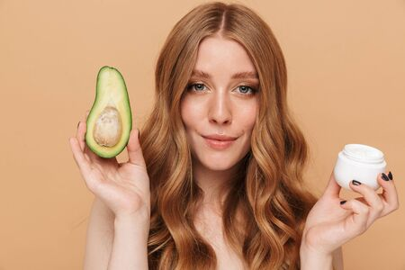 Portrait closeup of gorgeous young half-naked woman with long hair holding avocado and face cream jar isolated over beige background