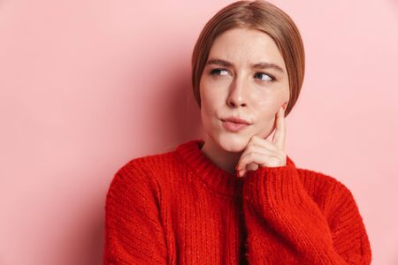 Photo of serious beautiful woman in red sweater posing and looking aside isolated over pink wall Imagens