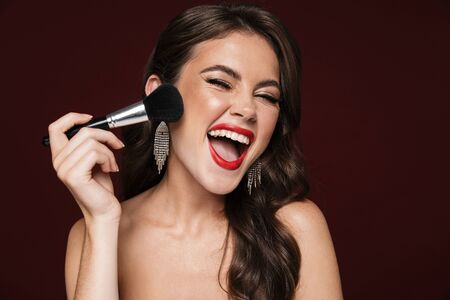 Image of excited shirtless woman wearing earrings laughing and using powder brush isolated over burgundy background Stock fotó