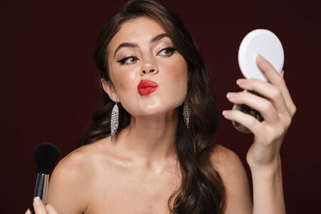 Image of sexual shirtless woman wearing earrings making makeup isolated over burgundy background