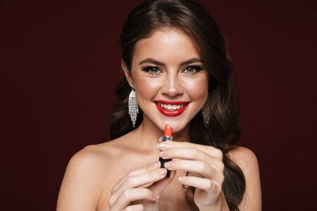Image of happy shirtless woman wearing earrings smiling and holding lipstick isolated over burgundy background