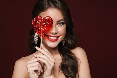 Image of happy shirtless woman wearing earrings smiling and holding candy isolated over burgundy background