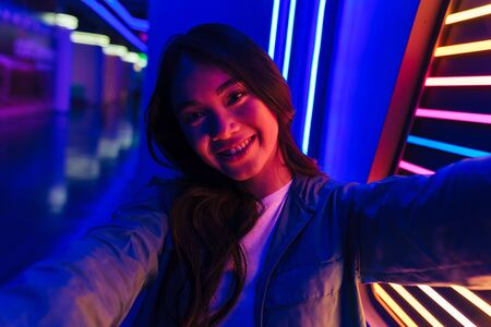 Photo of young happy optimistic positive woman posing over neon lights take a selfie by camera.