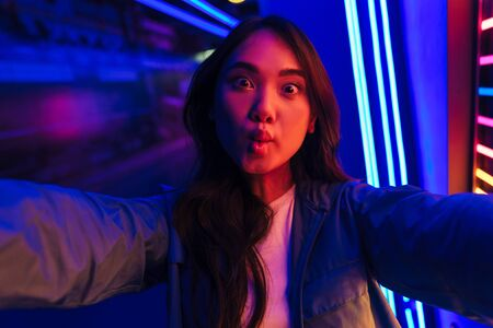 Photo of young funny positive woman posing over neon lights take a selfie by camera. Stock Photo