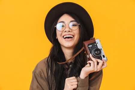 Image of young brunette asian tourist woman wearing hat using retro camera isolated over yellow background