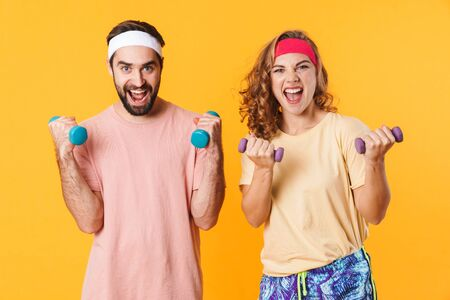 Portrait of athletic young happy couple wearing headbands smiling and lifting dumbbells isolated over yellow background