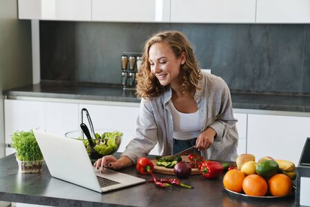Happy young woman making a salad at the kitchen, chopping vegetables, looking at laptop computer Foto de archivo