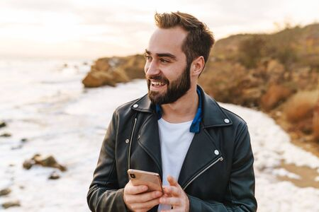 Handsome young bearded man wearing a jacket using mobile phone while standing at the beach