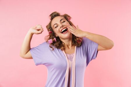 Image of young sleepy woman in curlers yawing with eyes closed isolated over pink background
