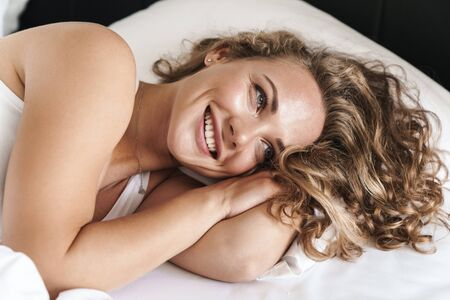 Close up of a happy beautiful young blonde haired woman laying on a pillow in bed 版權商用圖片