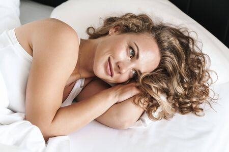 Close up of a smiling beautiful young blonde haired woman laying on a pillow in bed