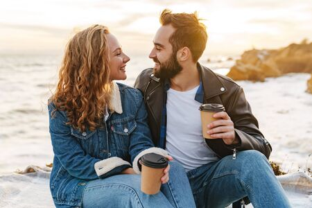 Image of beautiful young caucasian couple drinking coffee together while walking by seaside Stock Photo