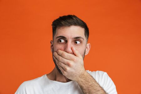 Image of young terrified man wearing basic white t-shirt covering his mouth with hand isolated over orange background Zdjęcie Seryjne