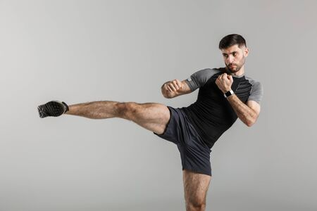 Image of a handsome strong sportsman fighter isolated over grey wall background make boxing exercises.