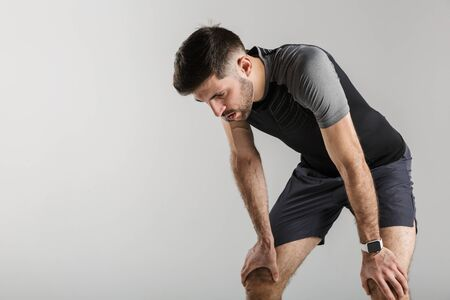Image of young tired man in sportswear resting while working out isolated over gray background
