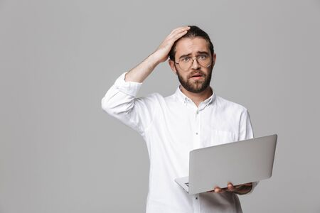 Image of a young confused handsome bearded man posing isolated over grey wall background wearing glasses using laptop computer.